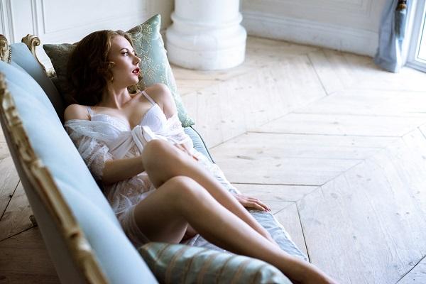 Dainty sexy Ukrainian girl lying on a soft bed wearing her underwear looking sideways dreamily