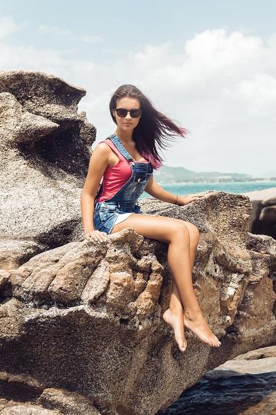Young beautiful Ukrainian girl wearing a denim overall sitting on huge rocks near the ocean shore