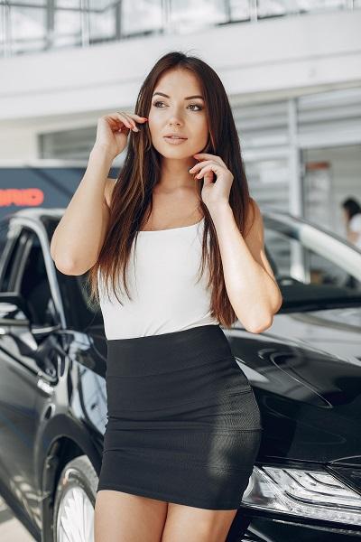 Stylish and elegant Ukrainian woman in a car salon wearing a short black skirt watching sideways